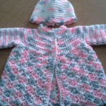 Kathy's biggest seller is baby sweaters - especially this adorable pink, grey, and white sweater with a matching hat.